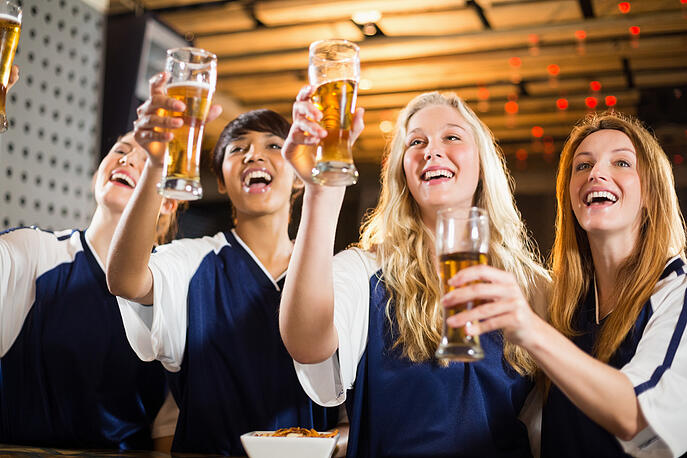 Group of smiling friends holding glass of beer in party at bar