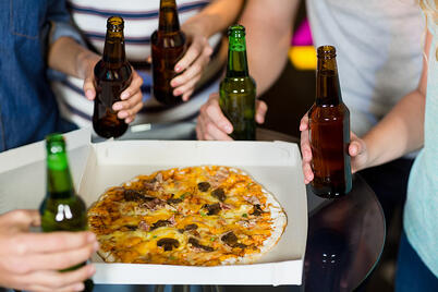 Mid section of friends having bottle of beer and pizza in party at bar